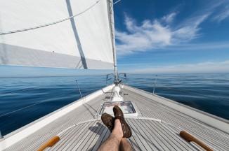Man's feet crossed on 62 ft sailboat